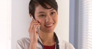 Chinese woman doctor talking on smartphone in office Stock Images