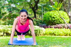 Chinese woman doing push-ups in park Royalty Free Stock Photography
