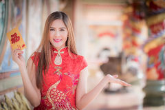 The chinese woman dress traditional cheongsam and hold red envelope. Asian woman in chinese dress holding couplet 'Happy ' (Chinese word) with chinese temple stock photo