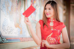 The Chinese woman dress traditional cheongsam and hold red envelope stock image