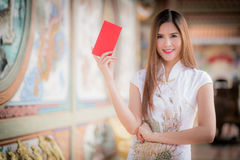 Chinese woman dress traditional cheongsam and hold red envelope. By background ambience China stock photography