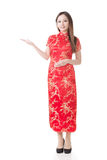 Chinese woman dress traditional cheongsam. Smiling Chinese woman dress traditional cheongsam and introduce on white background Royalty Free Stock Images