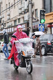 Chinese woman dressed in rainwear on an e-bike. Shanghai, China Royalty Free Stock Photography