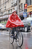 Chinese woman dressed in red rainwear, Shanghai, China. SHANGHAI–MAY 4, 2014. Chinese woman dressed in rainwear on a bicycle. Shanghai has a humid stock images