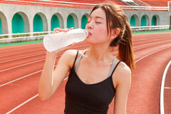 Chinese woman drinking water after jogging Royalty Free Stock Photography