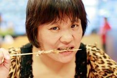 Chinese woman eating kebab royalty free stock photo