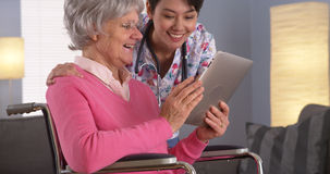 Chinese woman and Elderly patient talking with tablet Stock Images