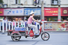 Chinese woman on electric freight bik. XIANG YANG-CHINA-JULY 1, 2012. Woman on electric freight bike on July 1, 2012 in Xiang Yang. Electric bikes are swarming Royalty Free Stock Photos