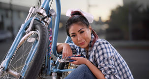 Chinese woman giving her bicycle a quick tuneup Royalty Free Stock Image