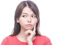 Chinese woman with hand on face, thinking Royalty Free Stock Image