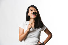 Chinese woman having fun with a fake mustache.  Stock Photography