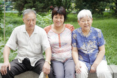 Chinese woman with her parents. Sitting in the garden Stock Photos