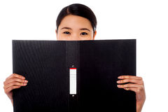 Chinese woman hiding face with business file Royalty Free Stock Photo