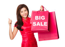 Chinese woman hold with shopping bag and thumb up for showing bi Stock Images