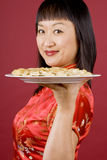 Chinese Woman Holding a Plate Full of Dumplings Royalty Free Stock Image