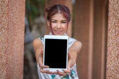 Chinese woman holding tablet black screen. Asian young girl wearing China Traditional dressing for Chinese new year culture. royalty free stock photography