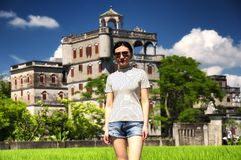 Chinese woman at Kaiping Tower Diaolou Scenic Area. A chinese woman standing at the edge of rice paddy at the historic buildings of Kaiping Diaolou in Zili royalty free stock images