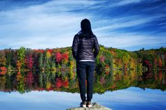 Chinese woman looking at the fall foliage in autumn. A chinese woman looking at the fall foliage reflecting in the water while sitting on a picnic table in royalty free stock images