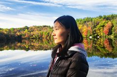 Chinese woman looking at the morning sun in autumn. A beautiful chinese woman looking at the morning sunlight in autumn at Burr Pond state park in torrington stock photo
