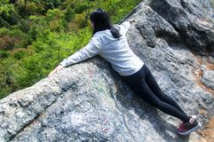 A chinese woman looking over a cliff. A chinese woman laying on top of the Black Rock cliff looking over at the trees below at Black Rock State Park in Thomaston stock photos