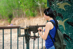 Chinese woman with an M60. A chinese woman at a gun range shooting a m60 mounted machine gun in South Vietnam Stock Photo