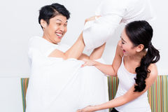Chinese Woman and man having pillow fight royalty free stock photo