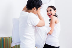 Chinese Woman and man having pillow fight stock images