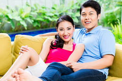 Chinese woman and man on sofa in their home Stock Photos