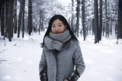 Chinese woman in a new england winter. A chinese woman looking at the camera outside in a wintry scene at white memorial conservation area in Litchfield stock photography