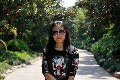 Chinese woman posing on a paved path Stock Photography