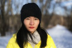 Chinese woman posing seriously at the camera. A beautiful Chinese woman wearing a yellow winter jacket looking at the camera on a cold winter day in Sheffield stock photo