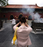 Chinese woman praying. A chinese woman praying in the Lama Temple of Beijing, China. The Yonghe Temple, also known as the Palace of Peace and Harmony Lama Temple royalty free stock photography