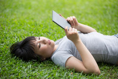 Chinese woman reading her e-book in park Royalty Free Stock Photo
