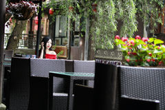 A Chinese woman in red dress in Feng Jing ancient town. Pictured in Feng Jing ancient town, a Chinese woman in Chinese red dress , sit on a chair, the chair is Royalty Free Stock Photos