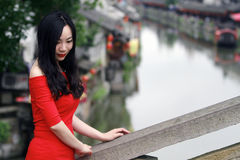 A Chinese woman in red dress in Feng Jing ancient town. Pictured in Feng Jing ancient town, a Chinese woman in Chinese red dress, stand on a stone ancient bridge royalty free stock photo