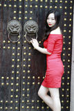 A Chinese woman in red dress in Feng Jing ancient town. She stand by a door which is Chinese traditional wooden door. there are two iron lion`s head on the royalty free stock photo