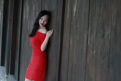 A Chinese woman in red dress lying on a woodern ancient door Royalty Free Stock Photo