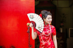 Chinese woman red dress traditional cheongsam. Close up portrait with red wood door Royalty Free Stock Photography