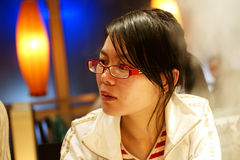 Chinese woman in restaurant. Thoughtful young Chinese woman in restaurant Royalty Free Stock Photography