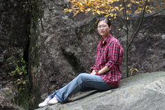 Chinese woman sat on rock. Young Chinese woman sat on rock on mountainside Royalty Free Stock Image