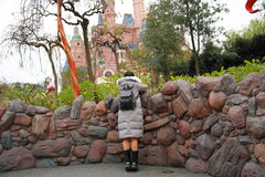 A Chinese woman in Shanghai Disney land. A Chinese girl in Shanghai Disney land, she looks at Disney castle, wears grey down jacket in winter, stands by a fence stock photography