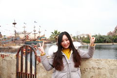 A Chinese woman in Shanghai Disney land. A Chinese girl in Shanghai Disney land, stand by a lake, there are several the Caribbean pirate ships behind her. Doing stock photography
