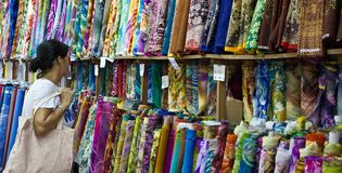 Chinese woman shops for fabric rolls at market stall royalty free stock photos