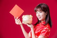 Chinese woman show piggy bank. Beauty woman show golden piggy bank and empty spring festival couplets in chinese new year royalty free stock image