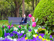 Chinese woman sitting on a bench Royalty Free Stock Photos