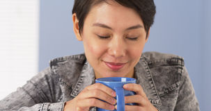 Chinese woman smelling cup of coffee Stock Images
