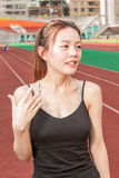 Chinese woman on sports track fanning herself Stock Photos