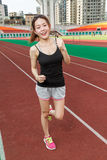 Chinese woman on sports track jogging Stock Images