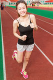 Chinese woman on sports track jogging Stock Photo