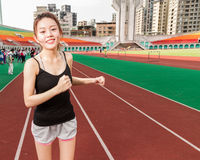 Chinese woman on sports track jogging Royalty Free Stock Image